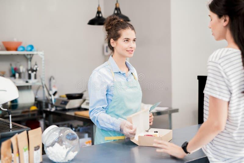 店主谈话与顾客在蛋糕商店 免版税图库摄影