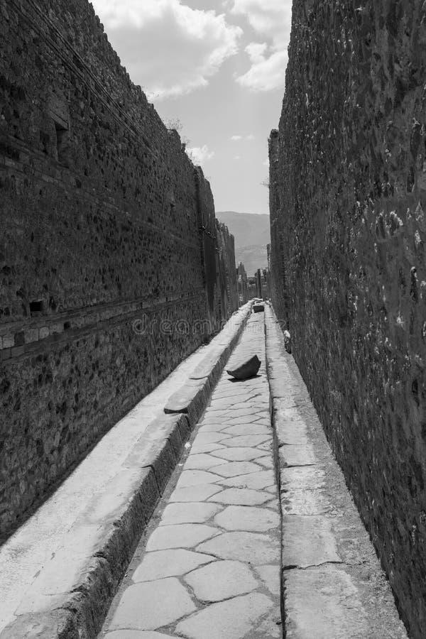 庞贝城意大利-与垫脚石的狭窄的通道 免版税库存图片