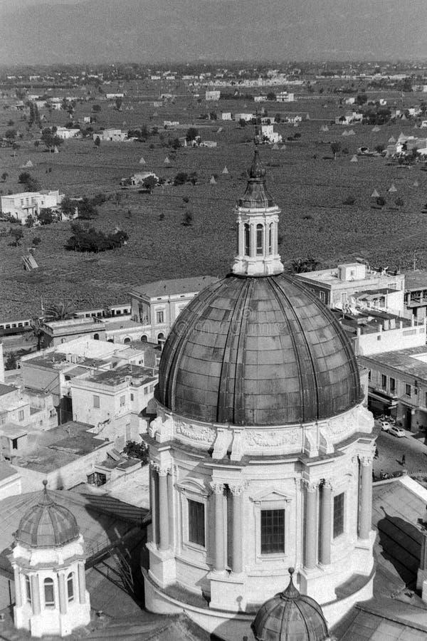 庞贝城,意大利,1961年-议院、乡下和农场形成背景对波纳佩的玛丹娜的圣所的圆顶 免版税库存照片