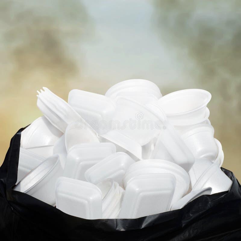 废垃圾泡沫食物盘子白色许多在塑料黑袋子堆肮脏在天空云彩空气大气污染背景 免版税图库摄影