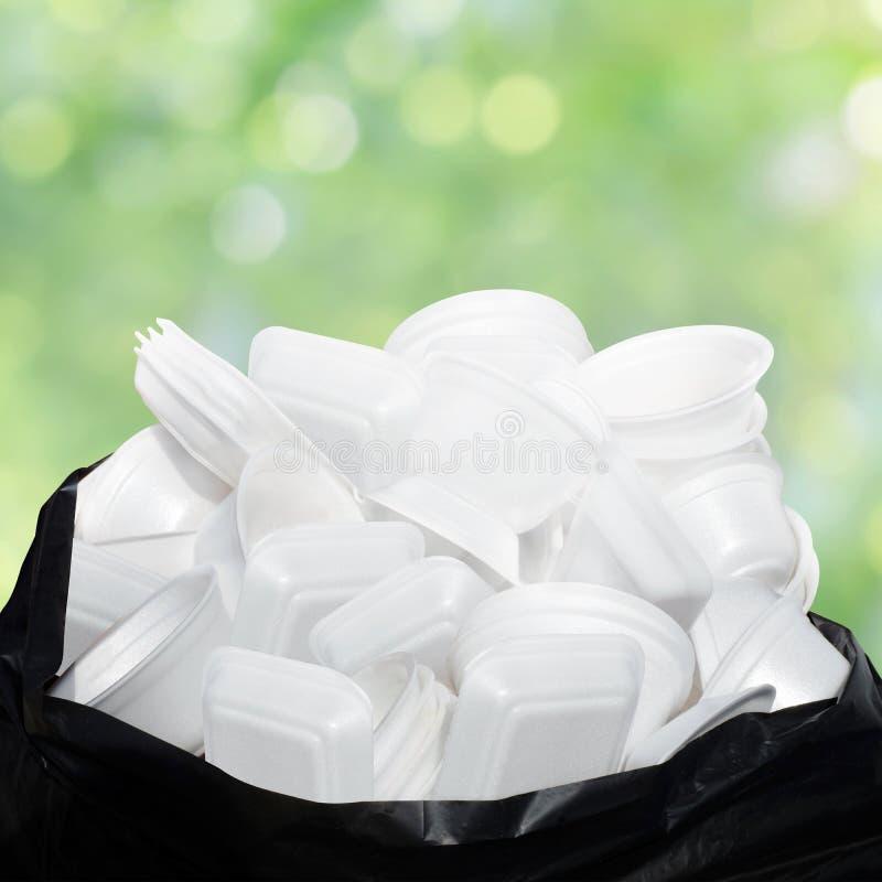 废垃圾泡沫食物盘子白色许多在塑料黑袋子堆肮脏在绿色自然bokeh背景 库存图片