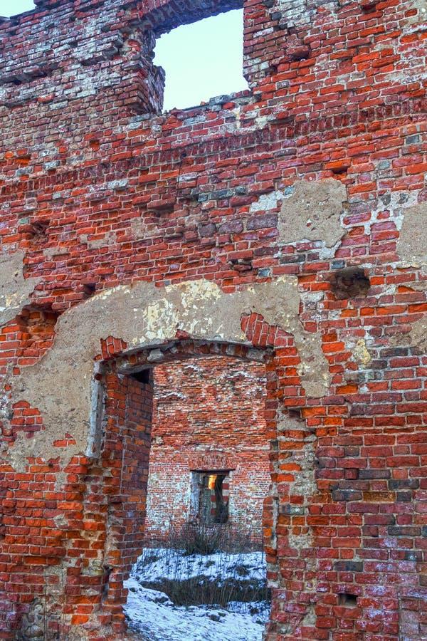 废墟房子破坏窗口门垂度的砖在荒原雪的中心保持仅外壁 免版税库存照片