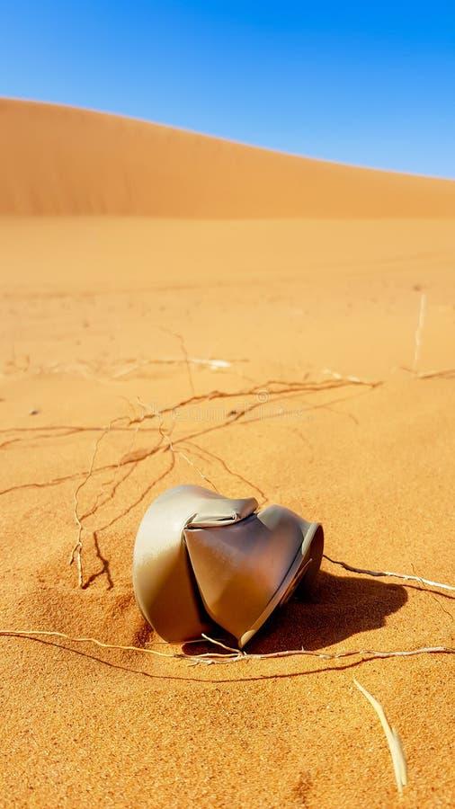 废弃物在沙漠,在沙子的生锈的罐头在沙漠 免版税图库摄影