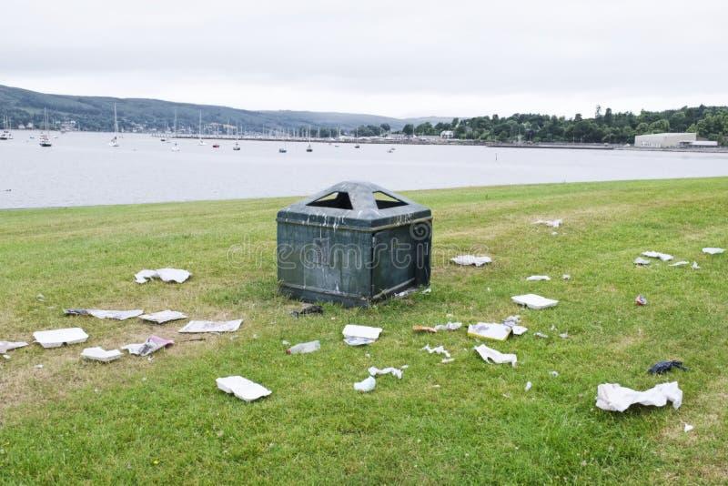 废弃物垃圾垃圾在公园在说谎在地面绿草废墟视图海滨胜地英国的容器外面 免版税库存图片