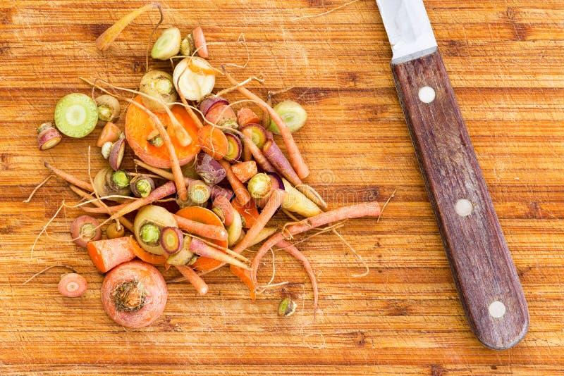 废弃从切口红萝卜的残余物在刀子旁边 库存图片
