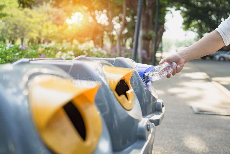废物管理,投掷塑料瓶的人入回收站 在下落前的废分离垃圾对保存的垃圾桶 库存照片