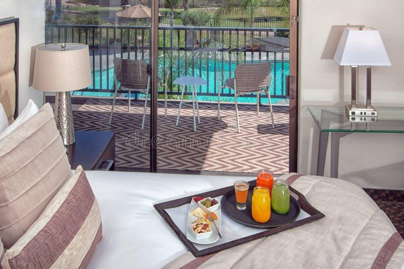 度假旅馆豪宅卧室床、椅子和书桌 免版税库存图片