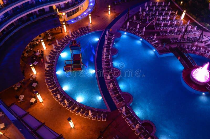 度假村游泳池周围在晚上 库存照片