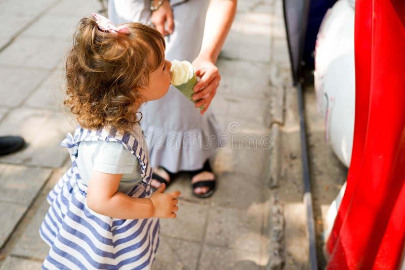 度过他们的周末在公园和吃冰淇凌的一年轻幸福家庭的特写镜头图象 免版税库存图片