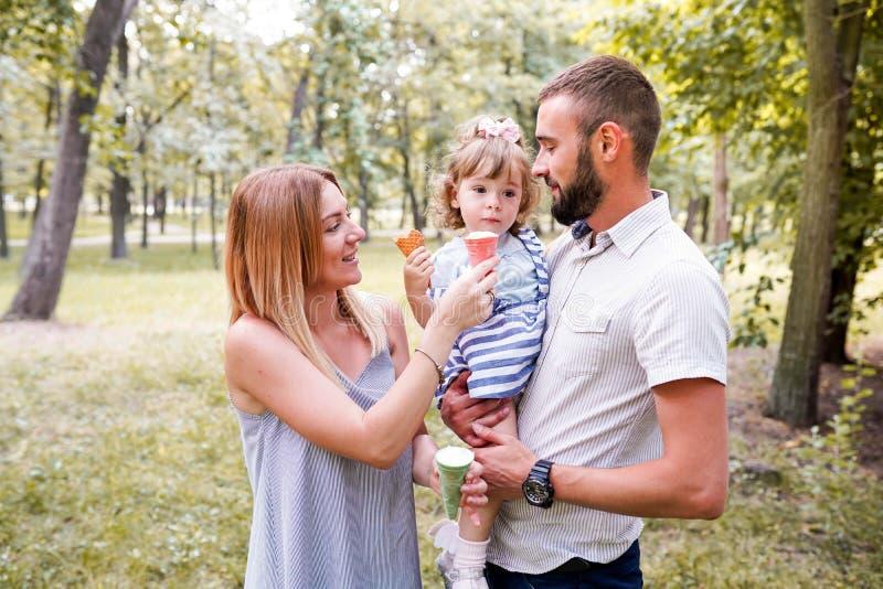 度过他们的周末在公园和吃冰淇凌的一年轻幸福家庭的特写镜头图象 免版税库存照片