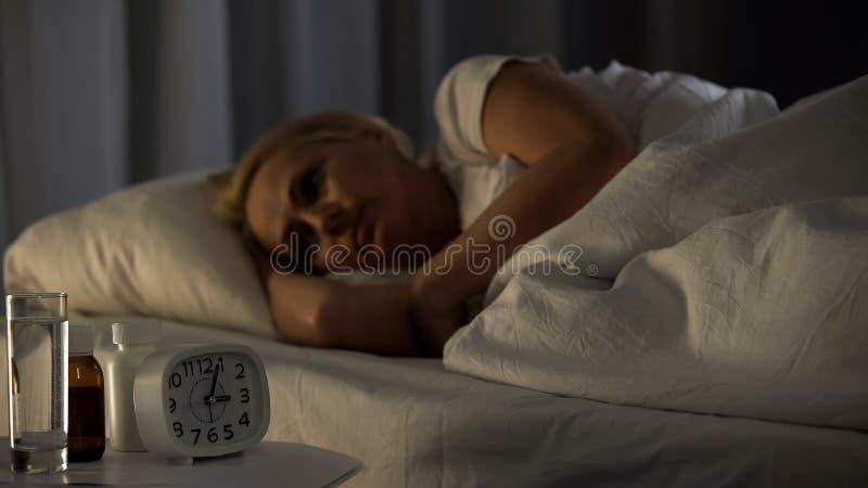 度过失眠的夜的成熟妇女在康复中心,感觉的痛苦 库存照片
