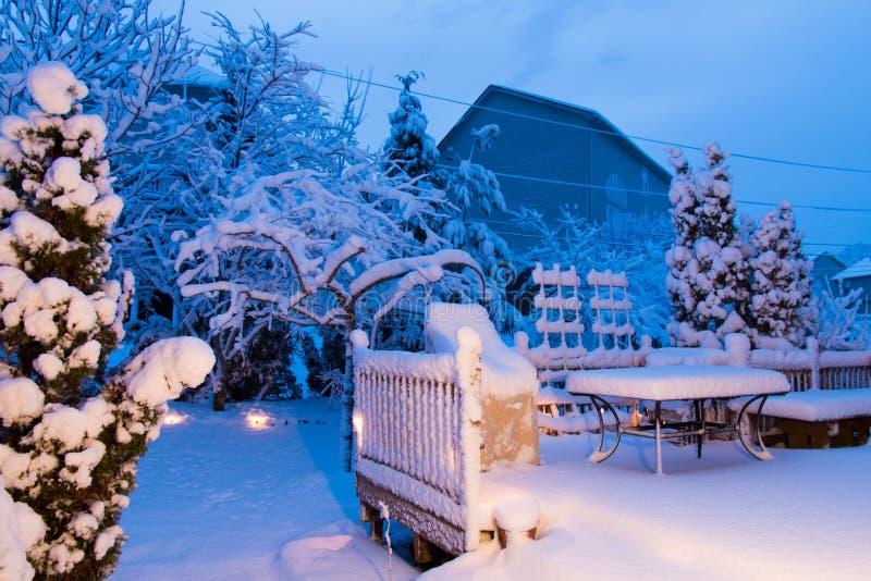 庭院和露台在降雪以后在晚上 库存照片