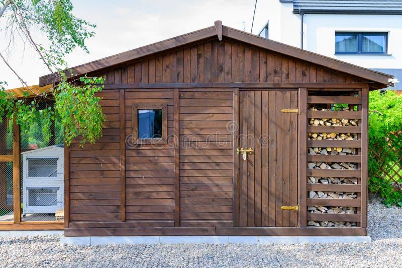 庭院在春天流洒了外部,有堆木材的棚的 库存图片