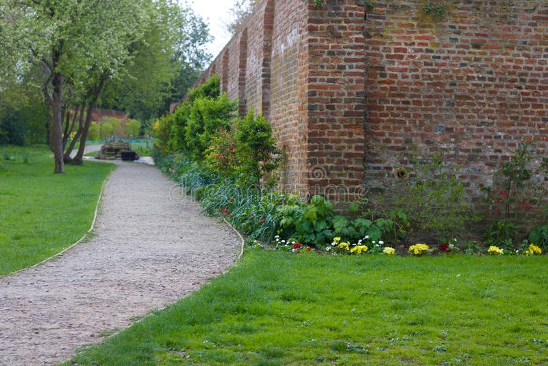 庭院场面有砖墙和地被植物植物的角落的陈列道路 免版税库存照片