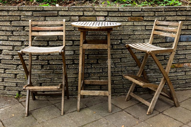 庭院家具家庭菜园两椅子一个桌棕色砖墙老葡萄酒咖啡馆 库存照片