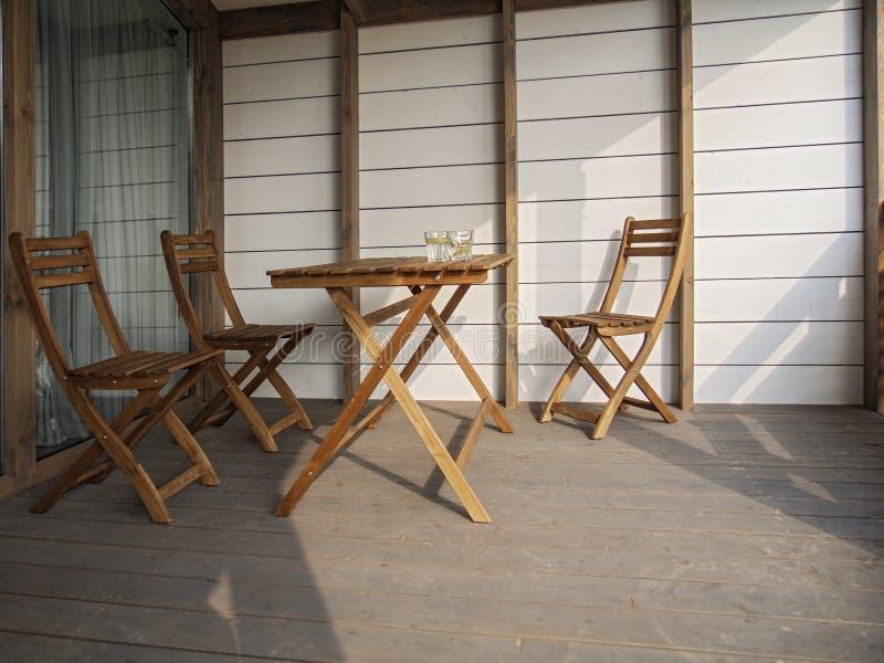 庭院木家具、两把椅子和一张桌在一栋乡间别墅里大阳台的或在旅馆里 在桌上是两块玻璃  免版税库存照片