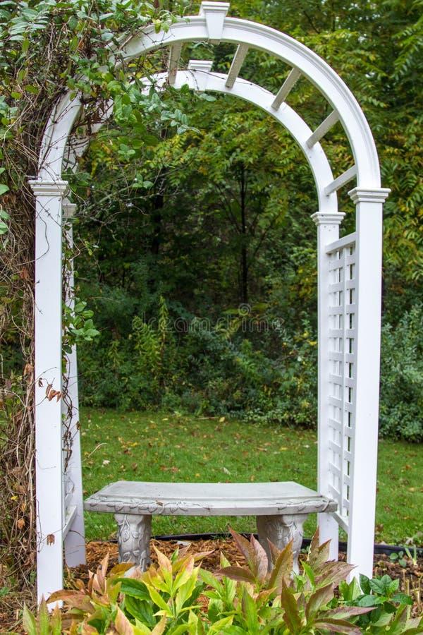 庭院树荫处和长凳在垂直的取向 免版税库存照片