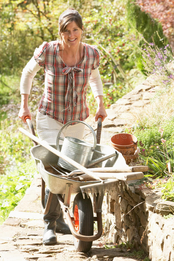 庭院独轮车妇女工作 免版税库存照片