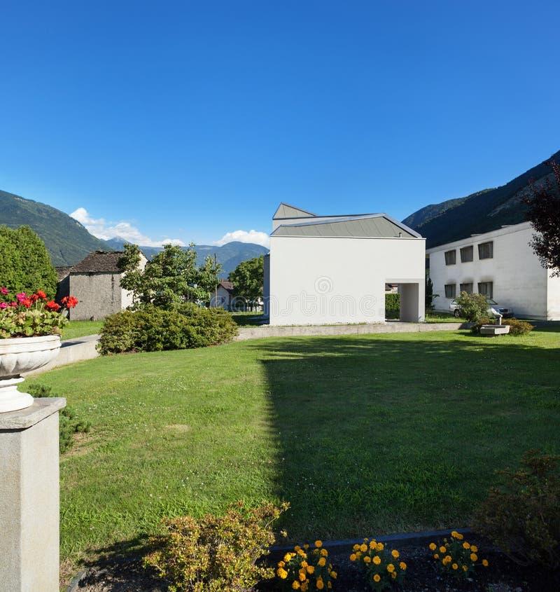 从庭院的白色房子视图 免版税库存照片