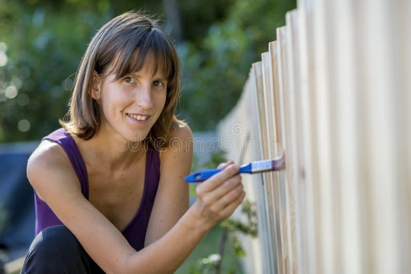 绘庭院篱芭的微笑的妇女 免版税库存照片