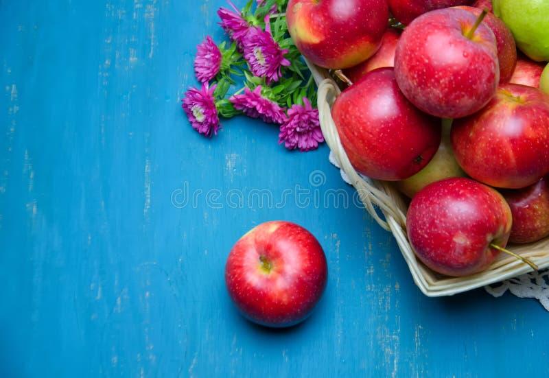 庭院花束开花在一个篮子的苹果在一张木桌上 免版税图库摄影