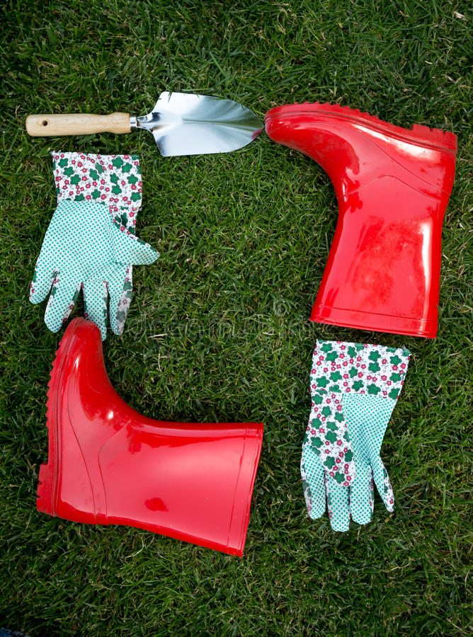 庭院说谎在绿草的手套、锹和红色胶靴 库存照片