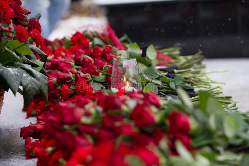 康乃馨开花哀悼的标志-在风和红色花的蜡烛在纪念碑 免版税库存图片