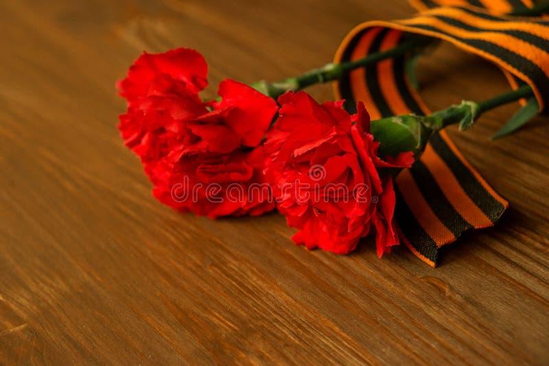 康乃馨花和乔治丝带在抽象轻的背景 9日历可以红色胜利 周年纪念70年 免版税库存照片