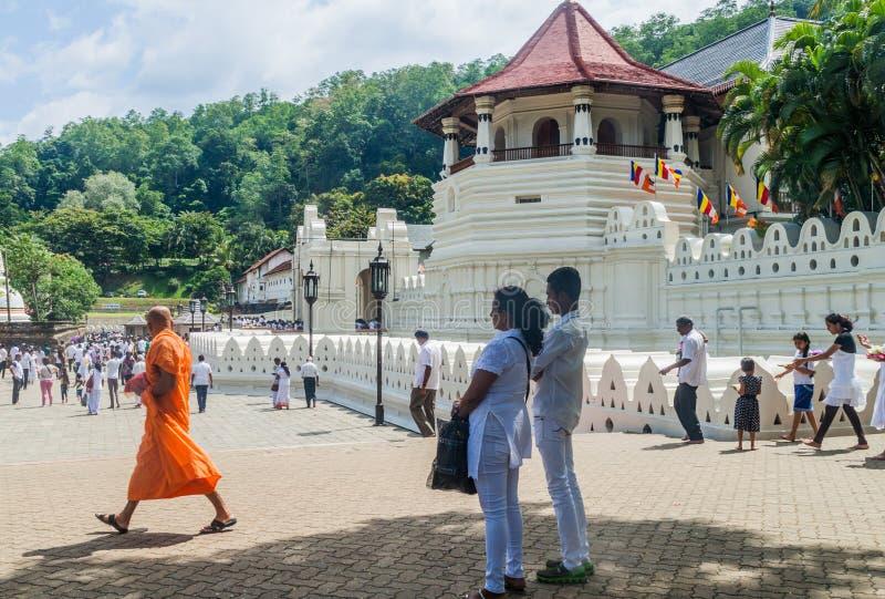 康提,斯里兰卡- 2016年7月19日:神圣的牙遗物的身穿白色衣的佛教献身者参观寺庙在Poya期间的 库存照片