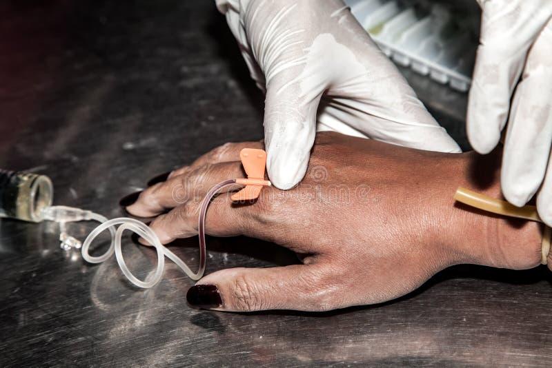 庸医用途对耐心手的注射器射入的手 免版税库存图片