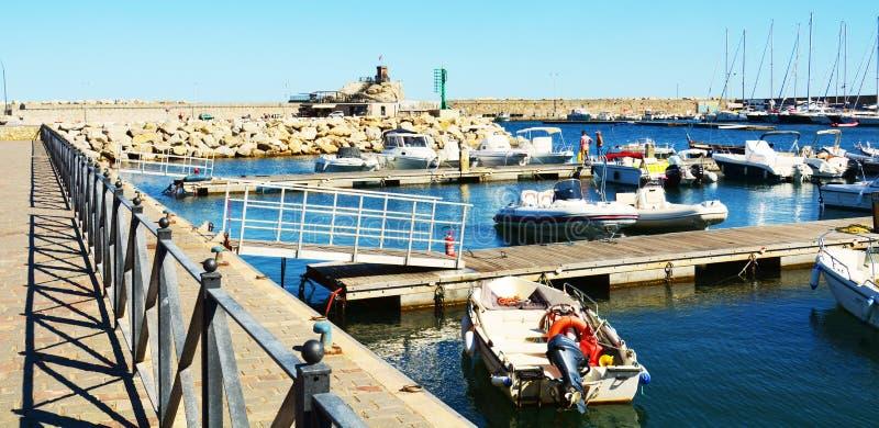 廖马里纳口岸、桥梁、岩石、波浪和小船在托斯卡纳,在厄尔巴岛海岛,意大利 免版税库存图片