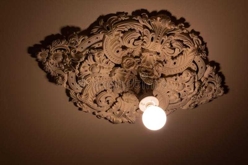 延长从一个极端华丽被熔铸的膏药天花板大奖章的光秃的电灯泡 免版税库存图片