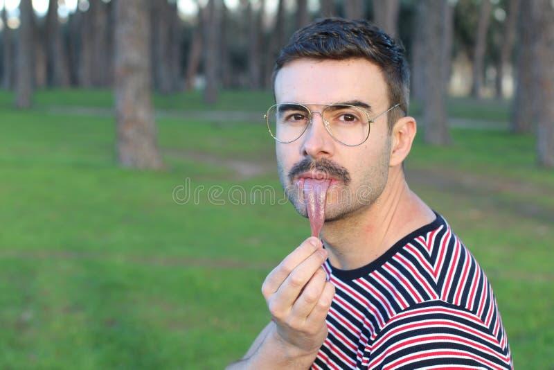 延长他的舌头的人的奇怪的图象  免版税库存照片