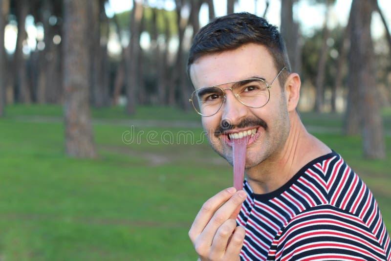 延长他的舌头的人的奇怪的图象  库存图片