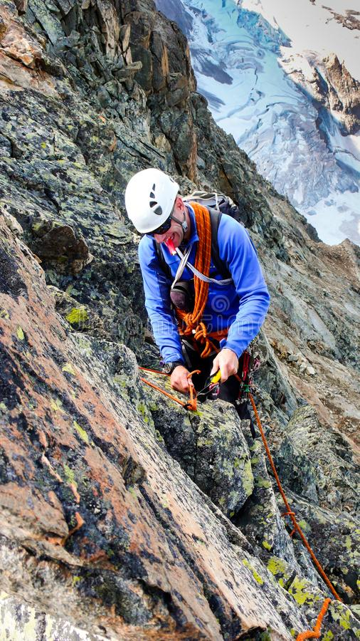 建立与岩钉的男性山指南传统套住姿态从一个高高山峰顶坐式下降法 库存图片