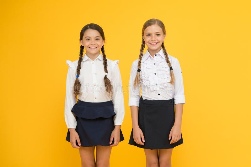 建立孩子的更加明亮的未来 逗人喜爱的矮小的女小学生愉快微笑在黄色背景 一起去 库存图片