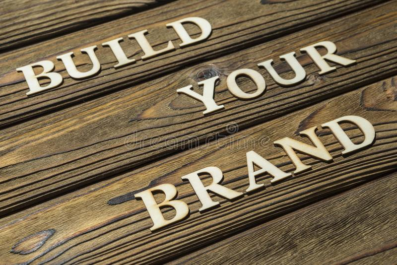 建立您的品牌文本由在木背景的信件组成 免版税库存图片