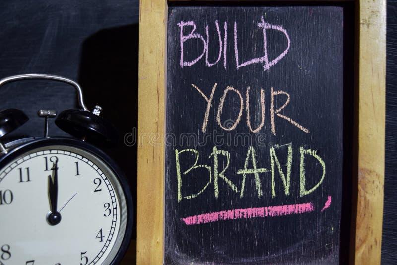 建立您的在词组五颜六色手写的品牌在黑板 库存照片