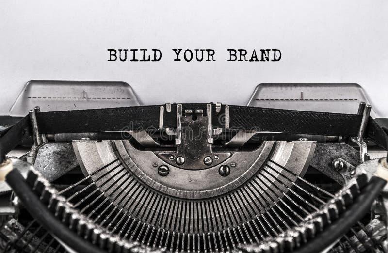 建立您的被键入的品牌在老葡萄酒打字机的词 关闭 库存照片