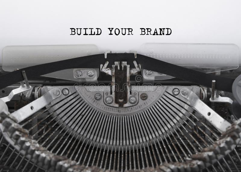 建立您的被键入的品牌在葡萄酒打字机的词 免版税库存图片