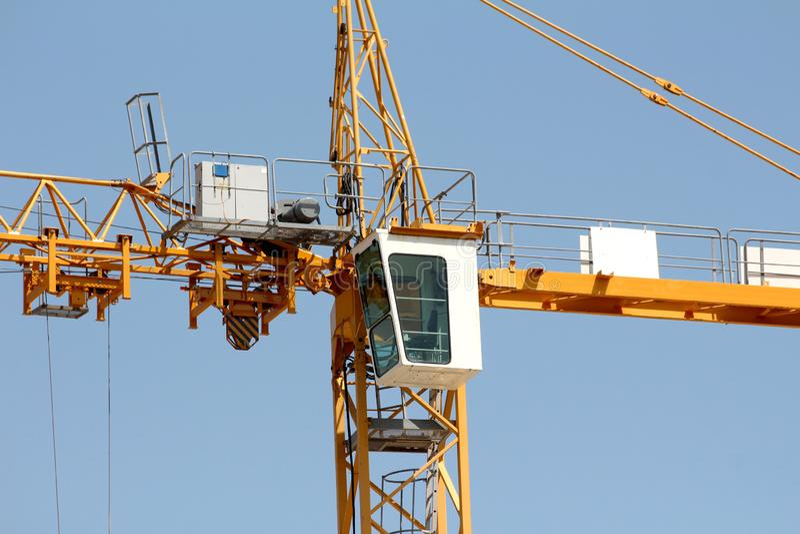建筑业塔吊或TC中央操纵站驾驶舱在起重机的一边登上了在地方工地工作 库存照片