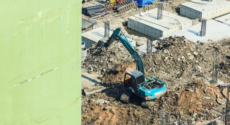 建筑业,混凝土建筑建造场所 具体堆被驾驶到地面被挖掘机在基础坑 免版税库存照片