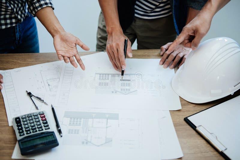 建筑学工程师配合会议,画和运作为在工作场所,概念的建筑项目和工程学工具 免版税库存图片