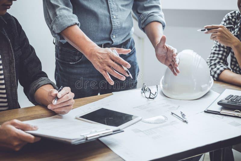 建筑学工程师配合会议,画和运作为在工作场所,概念的建筑项目和工程学工具 免版税图库摄影