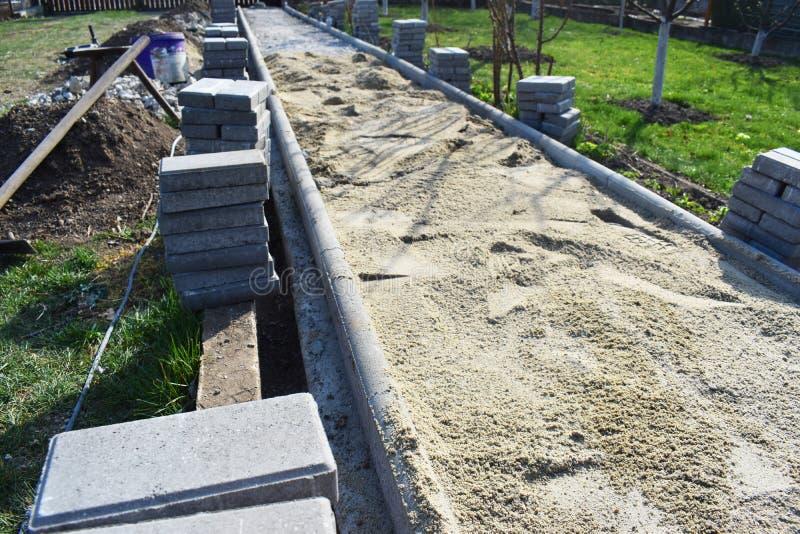 建筑工人在工地工作放置小径工作的混凝土路面石头 铺路石工作者投入 免版税库存图片