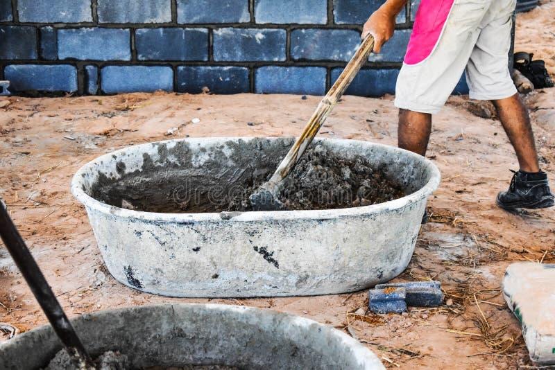 建筑工人混合在建筑业的水泥 免版税库存照片