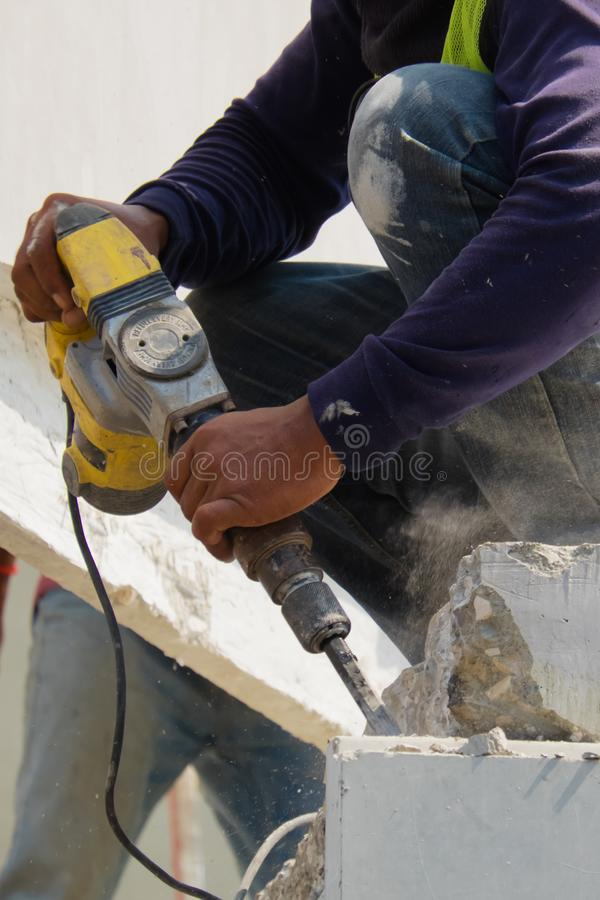 建筑工人用途电钻钻井混凝土墙在建筑区域,预铸的房子建筑 库存图片
