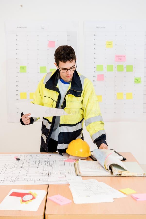 建筑工人转动的页,当拿着图纸时 免版税库存图片