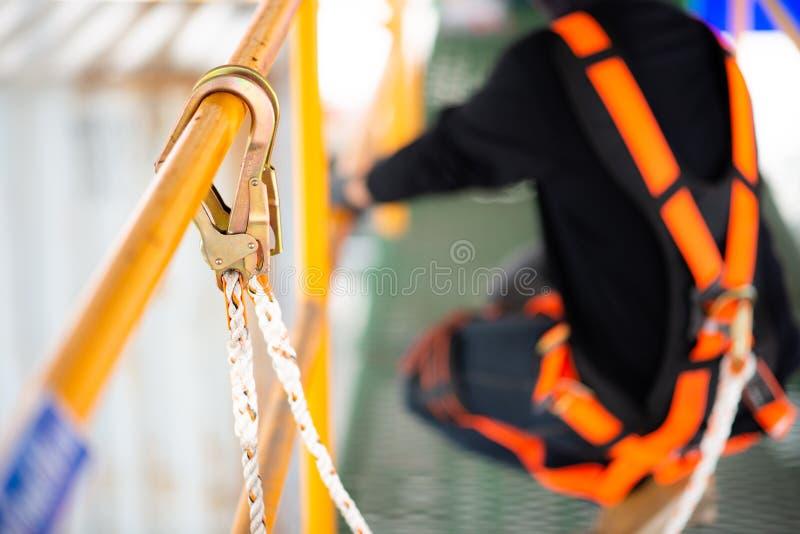 建筑工人运作在建筑的佩带的安全带和安全线 免版税库存照片