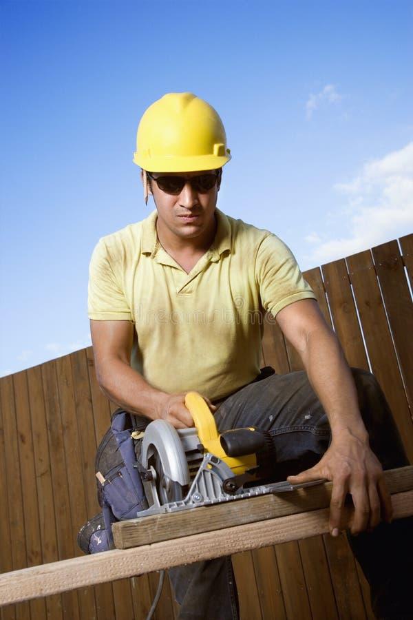 建筑工人锯切木头 免版税库存照片